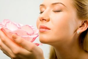Woman smelling pink flower.