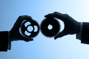 Shadowed hands holding cogs against blue background.