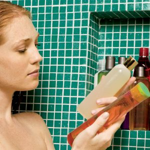 Woman choosing between two shampoos in the shower.