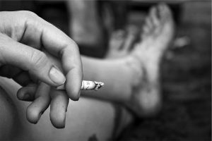 Hand holding cigarette with feet crossed in front.
