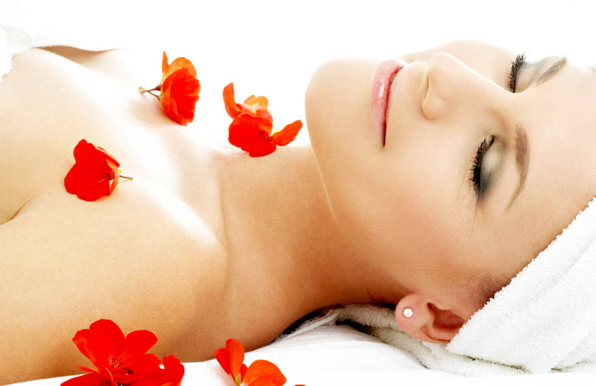 Woman lying down with hair in towel covered in red petals.