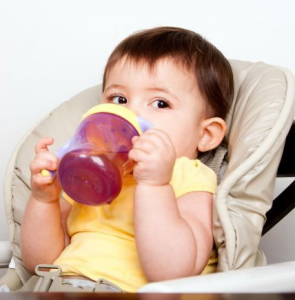 Baby in baby seat drinking from sippy cup.