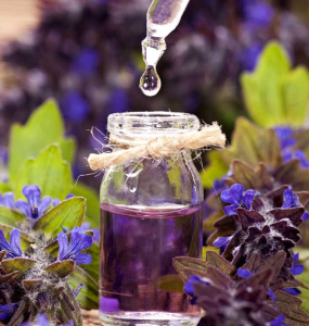 Small bottle of purple liquid surrounded by purple flowers.
