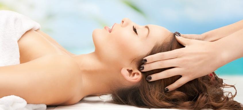 Woman lying down getting head massaged.