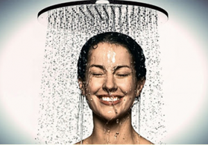 Woman under shower smiling.