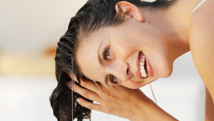 Woman smiling washing her hair.