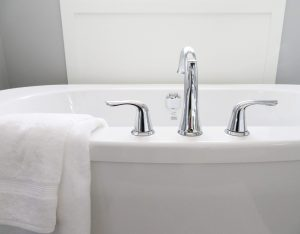 White bath with towel and silver faucet.