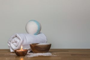 Towel rolled up with bath bomb balanced on top next to candle.