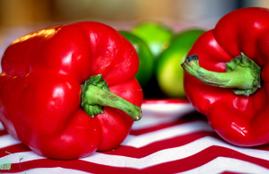 Two red peppers on red and white cloth.