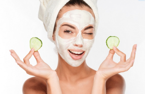 Woman with hair in towel wearing face mask holding cucumber slices.