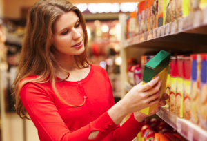 Woman reading the ingredients label on food package in supermarket.