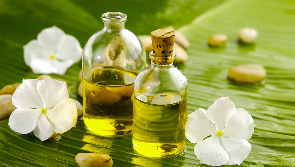 Two small bottles of oild surrounded by white flowers.