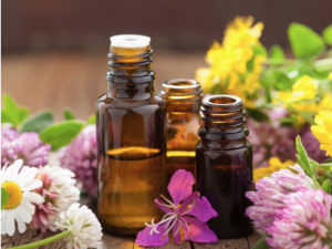 Small bottles of oil surrounded by flowers.