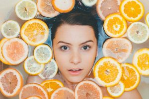 Woman surrounded by sliced citrus fruit floating in water.
