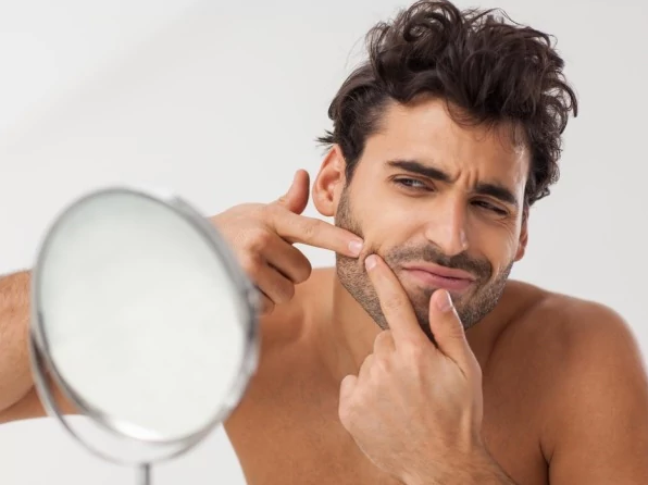 Man looking into a mirror and popping a pimple.
