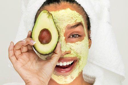 Woman wearing an avocado mask while holding half an avocado.
