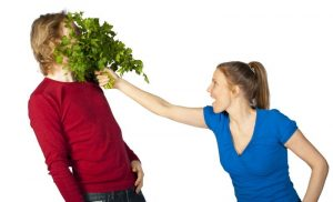 Woman putting bouquet of herbs in man's face.