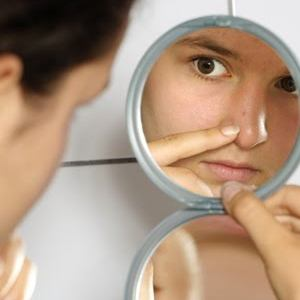 Woman looking at pores in mirror.