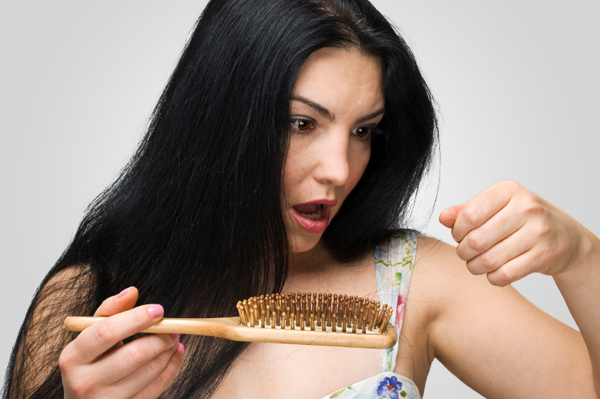 Woman pulling hair out of her brush,