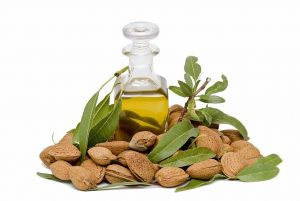 Bottle of oil surrounded by almonds.