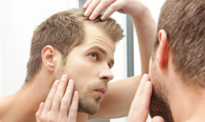 Man looking at own scalp.