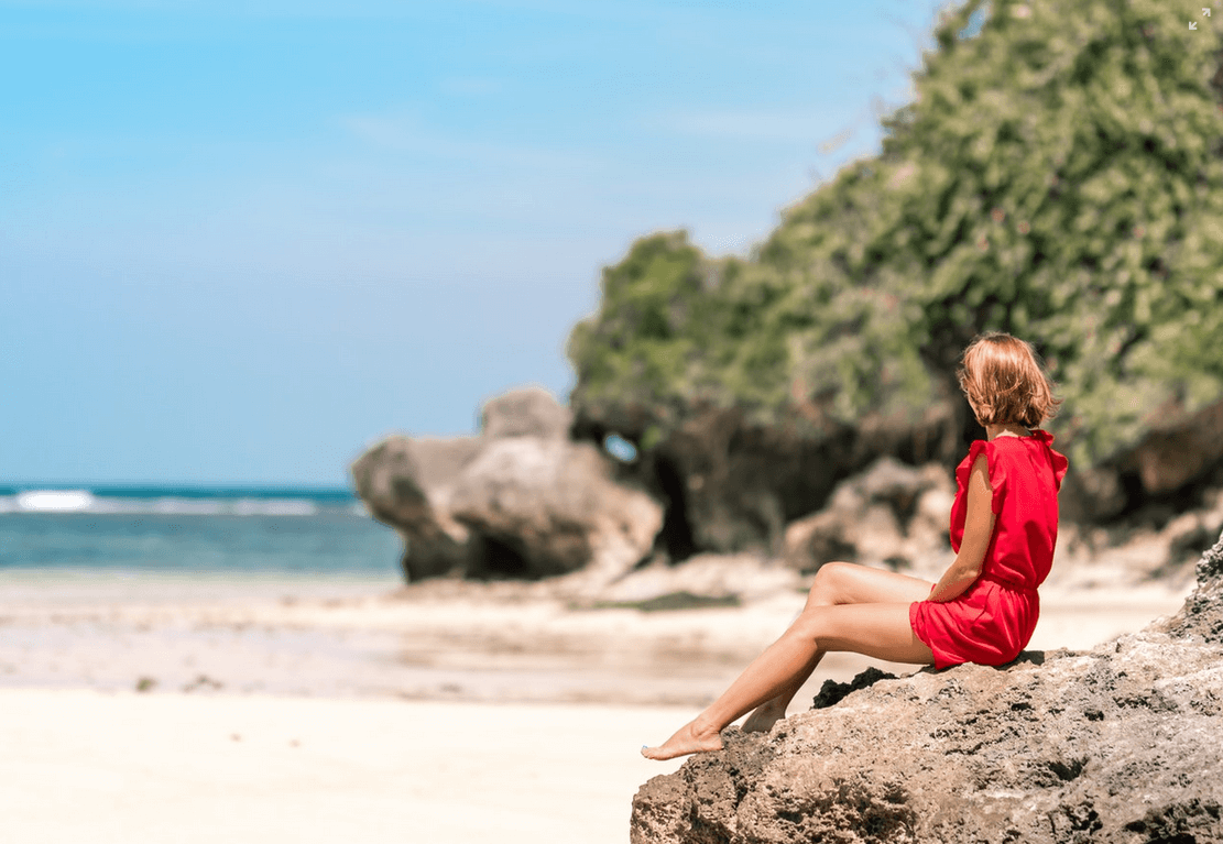 Woman in red dress sitting by the beach.