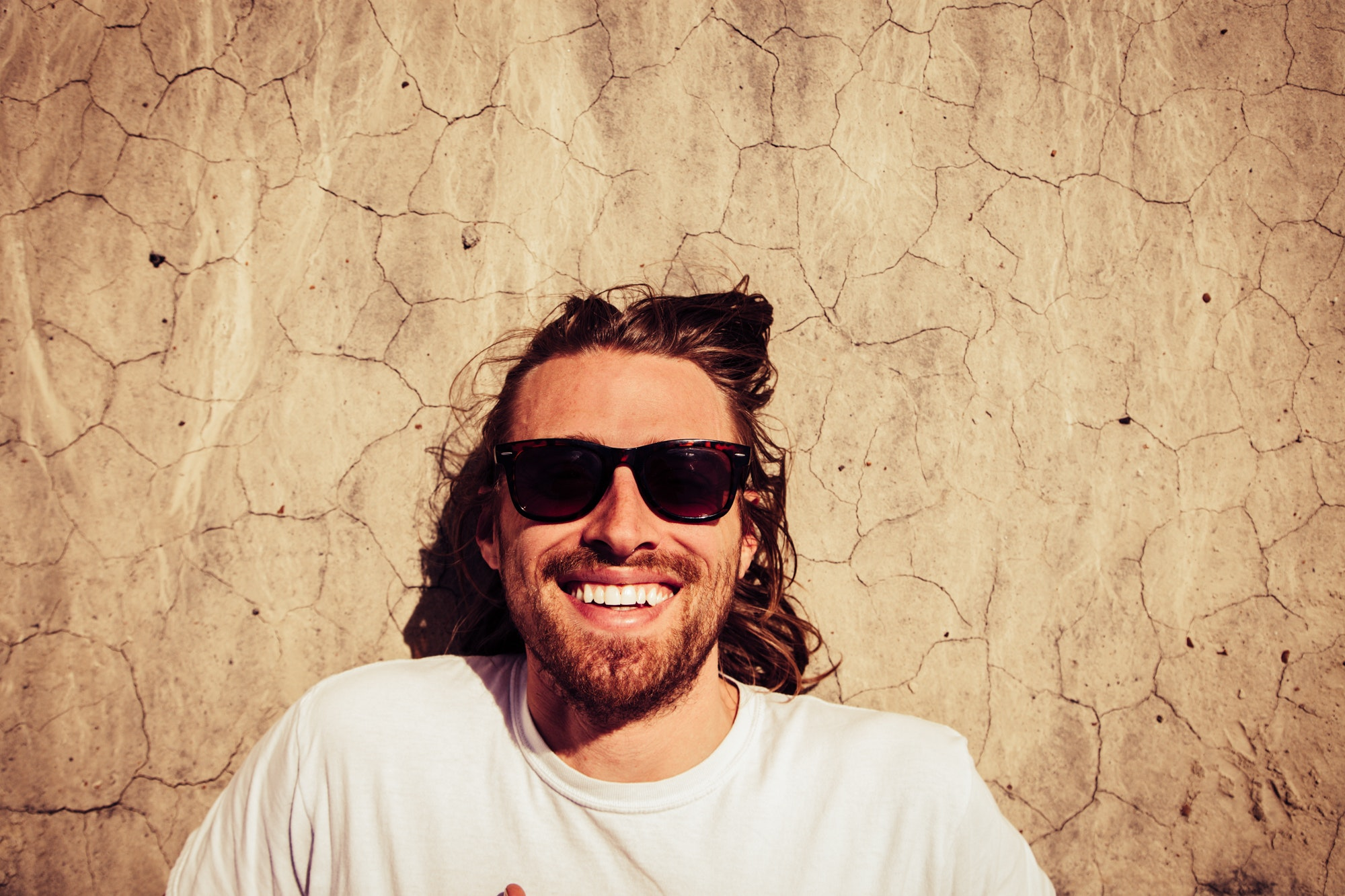 Man with long hair smiling wearing sunglasses while laying on floor.