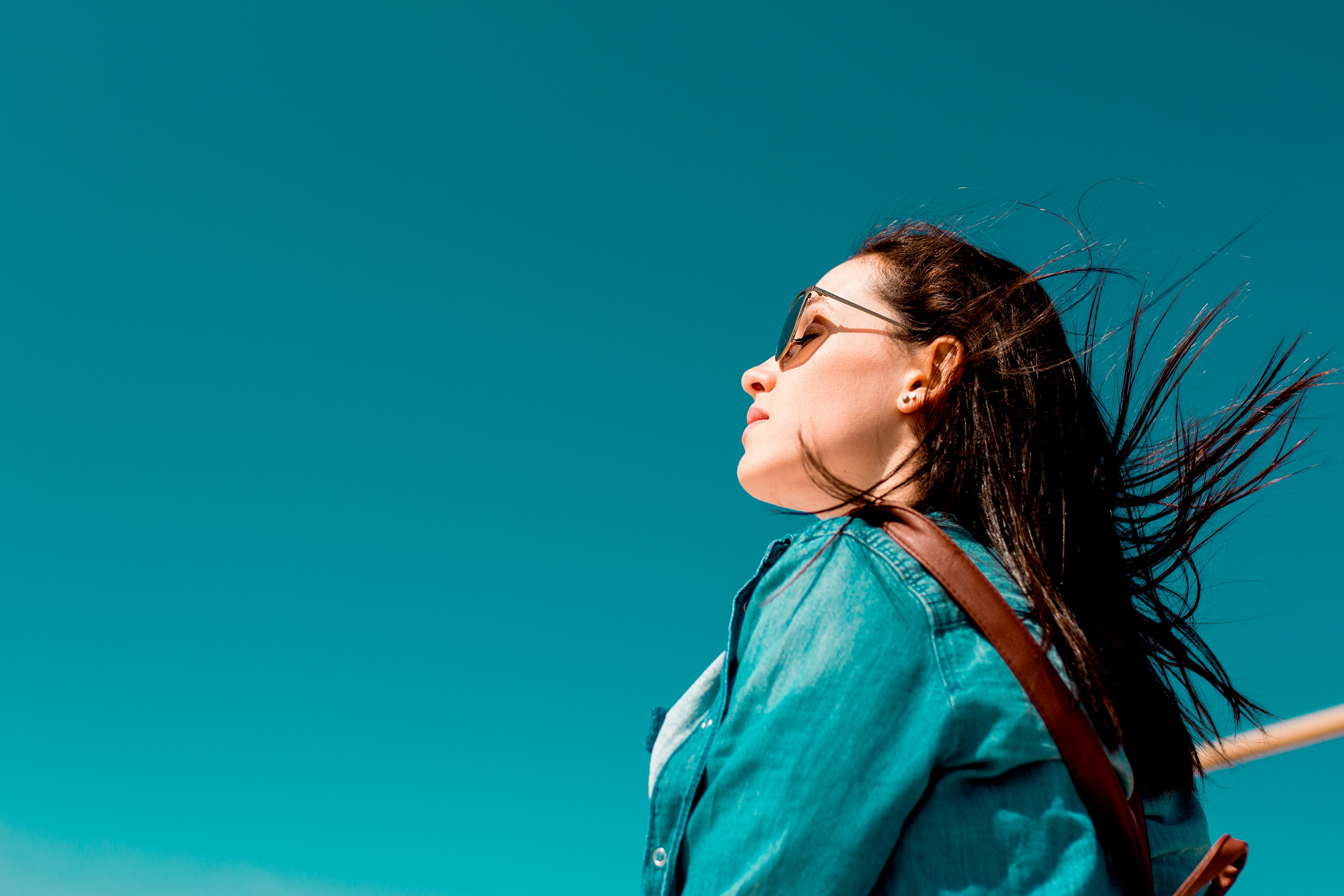 Woman wearing sunglasses enjoying the breeze with the sky in background.
