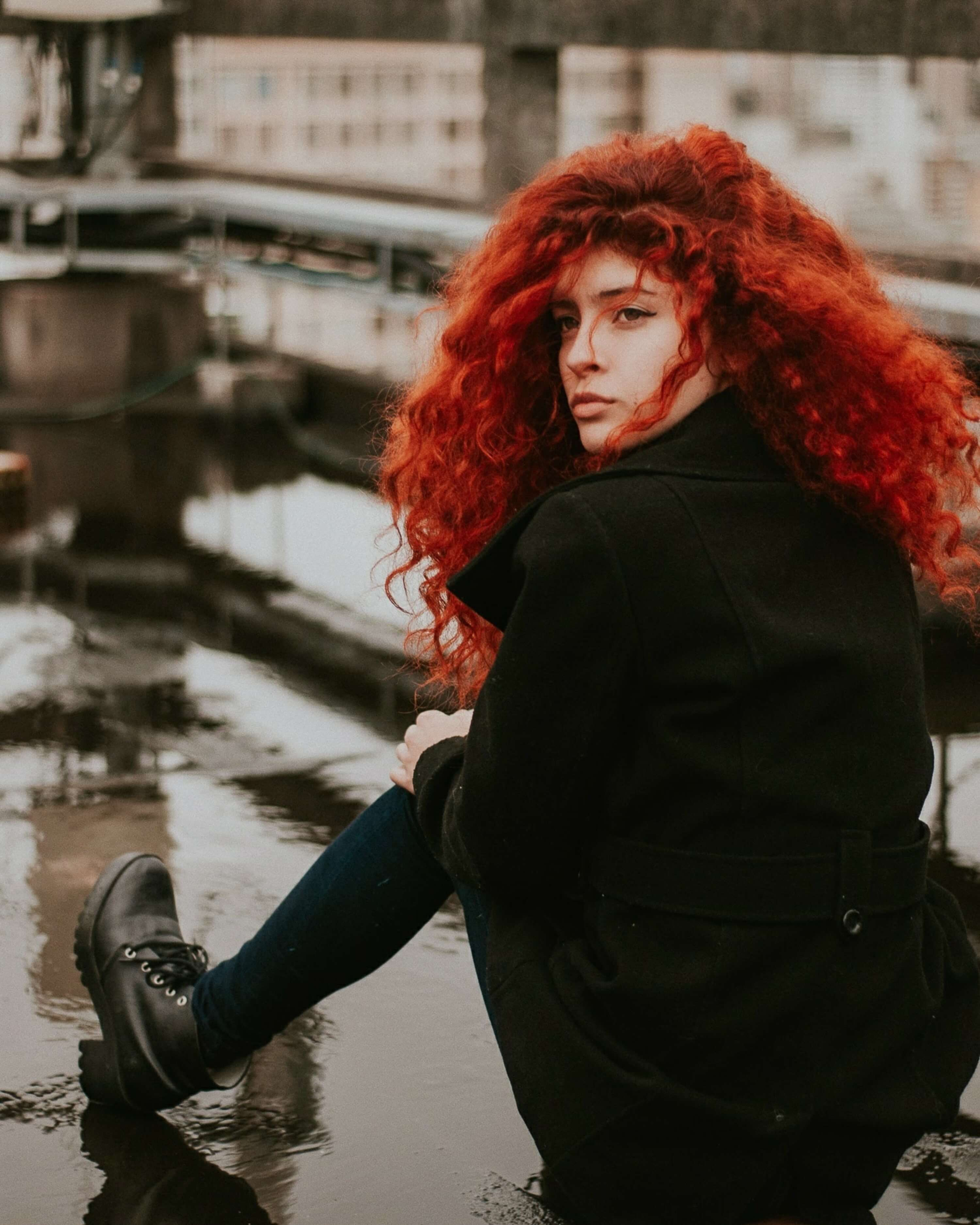 Woman with red curl hair looking back.