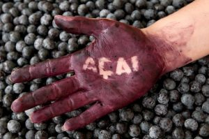 Hand covered in berry juice with acai written.
