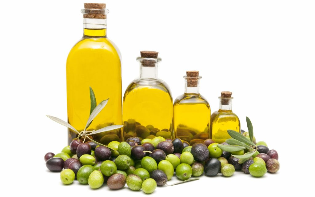 Four different sized bottles of oil surrounded by olives.