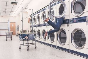 Woman trying to get out of washing machine in laundromat.