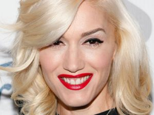 Gwen Stefani smiling with red lips.