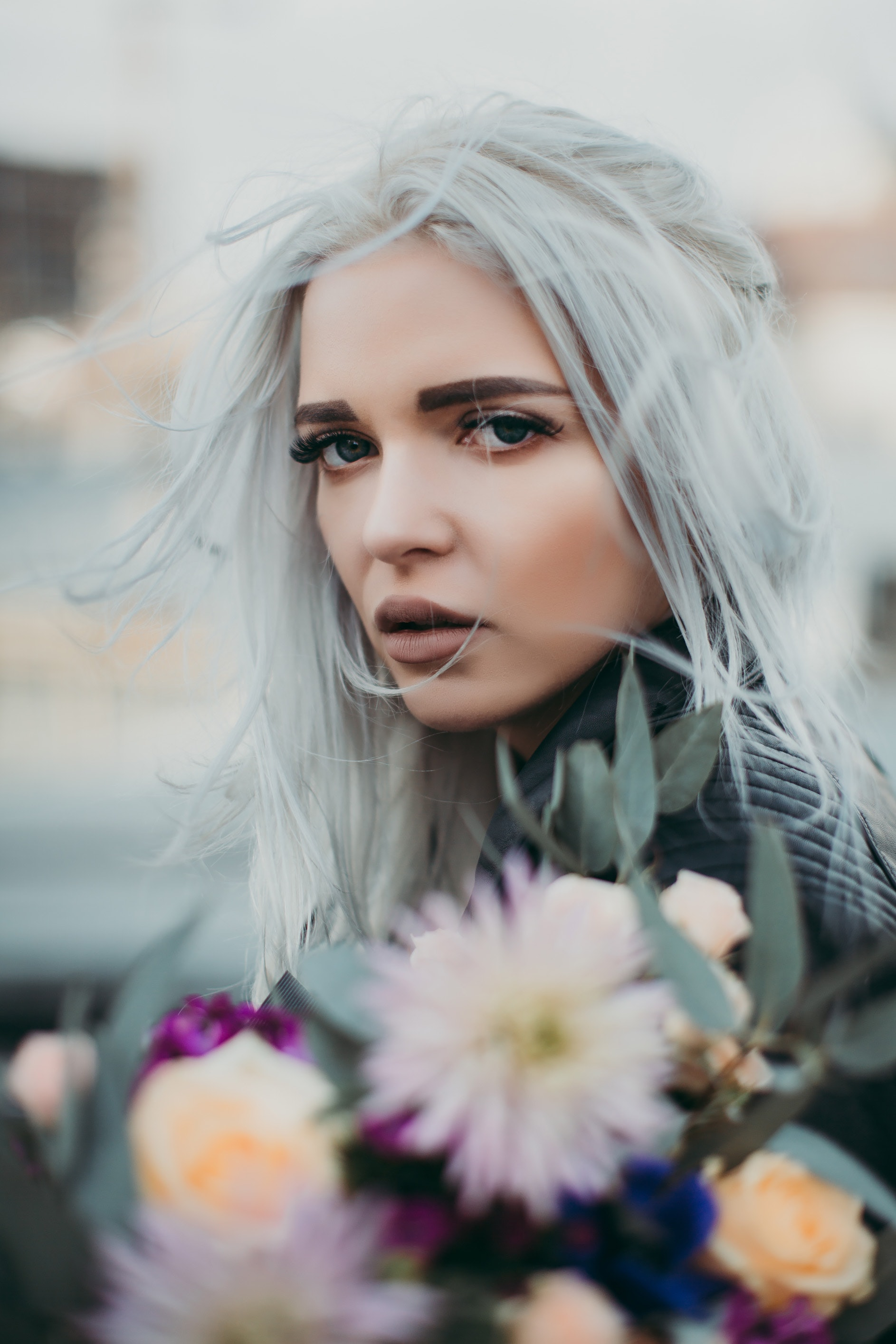Woman with silver hair surrounded by flowers.