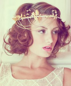 Woman with curly, brown hairy wearing gold flower crown.
