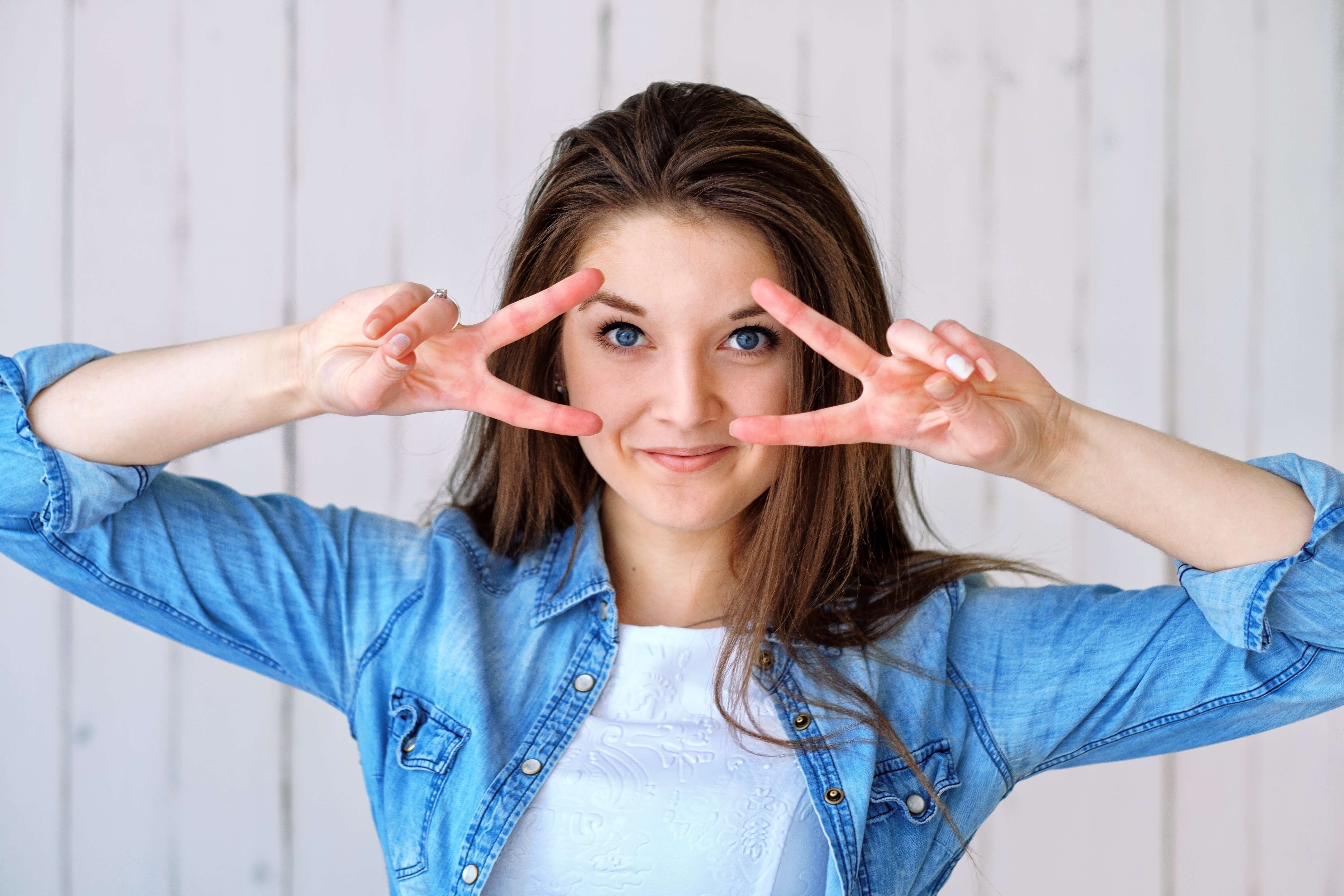 Woman holding up her finger in peace signs by her eyes.