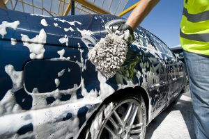 Man washing a car with sponge.