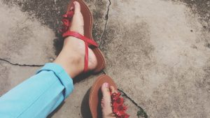 Red sandals worn by a woman.