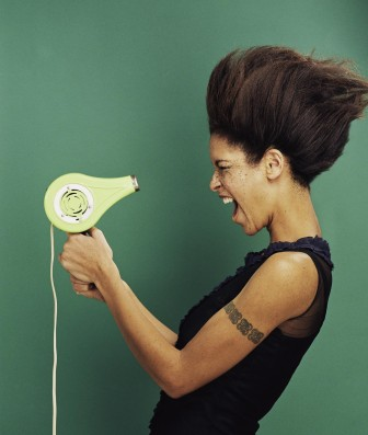 Woman screaming into a hair dryer.