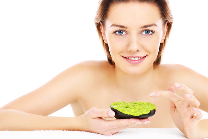 Woman about to dip her finger in a mushed avocado.