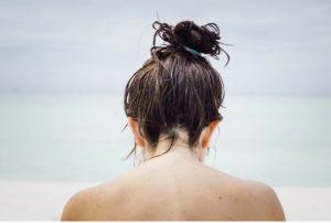Back of woman with wet hair in a bun.