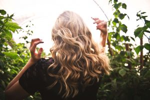 Back of blonde-haired woman in greenery.