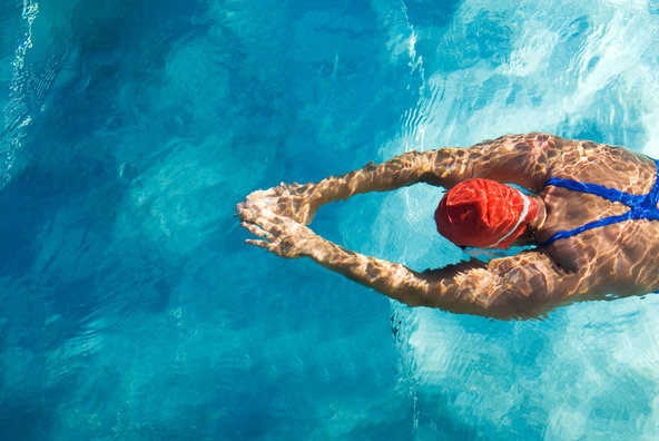 Woman wearing swim cap swimming in pool.