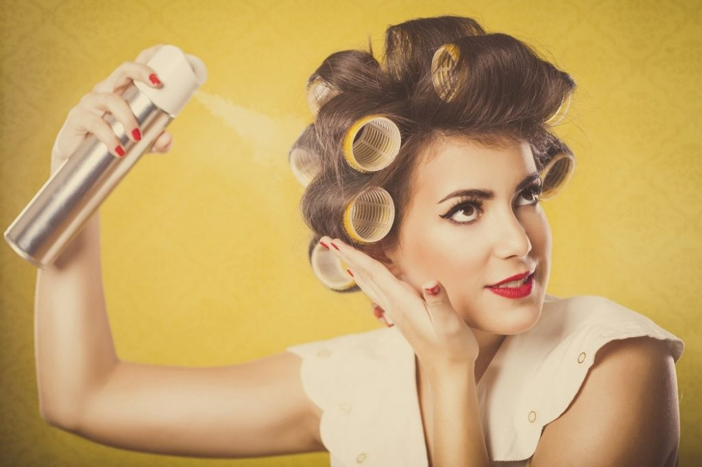 Woman in curlers applying hairspray