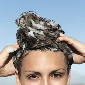 Woman lathering soap into her hair.