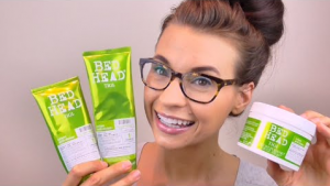Woman in glasses holding bed head products.