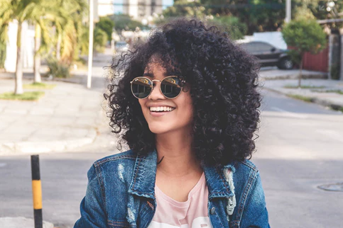 Smiling woman with curly hair wearing sunglasses.
