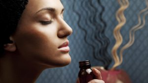 Woman smelling brown glass bottle.