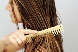 Woman combing her wet hair.