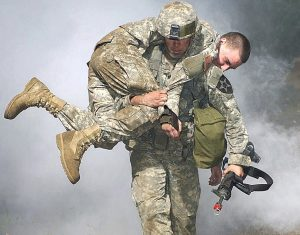 Soldier carrying another soldier on his back.